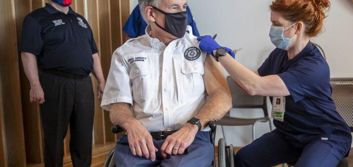 注册护士April Burgeons在2020年12月22日,星期二在Ascension Seton医疗中心向得克萨斯州州长Greg Abbott注射了一剂Pfizer-BioNtech COVID-19疫苗。服务最左侧,注册护士Toby Hatton继续看。 (里卡多·B·布拉泽尔/奥斯汀美国政治家,通过美联社)