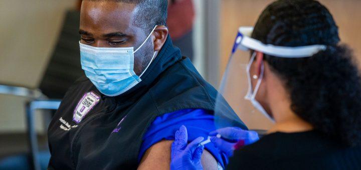 "COVID单位护士Tonychris"" TC"" Nnaka,(左)在12月15日在Parkland医院举行的媒体活动中,从职业健康总监Stephanie Collins那里接受了辉瑞的COVID-19疫苗接种。"